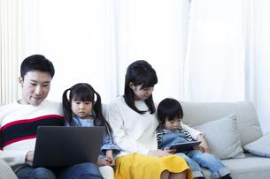 パソコンとタブレットを見る家族の写真素材 [FYI04317002]
