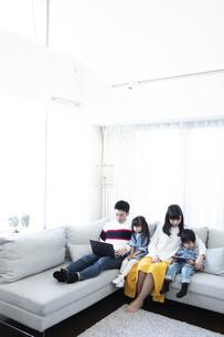 パソコンとタブレットを見る家族の写真素材 [FYI04317003]