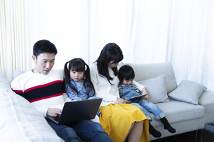 パソコンとタブレットを見る家族の写真素材 [FYI04317004]