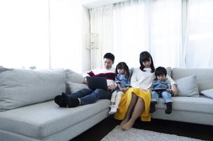 パソコンとタブレットを見る家族の写真素材 [FYI04317005]
