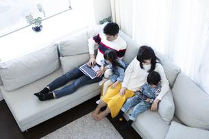 パソコンとタブレットを見る家族の写真素材 [FYI04317007]