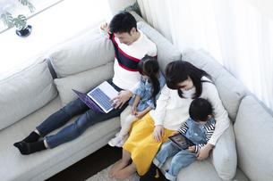 パソコンとタブレットを見る家族の写真素材 [FYI04317010]