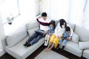 パソコンとタブレットを見る家族の写真素材 [FYI04317011]