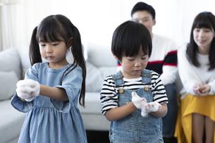 泡を持った子供たちと見守る夫婦の写真素材 [FYI04317026]