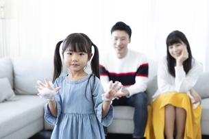 手を洗う女の子と見守る夫婦の写真素材 [FYI04317030]
