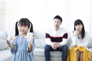 手を洗う女の子と見守る夫婦の写真素材 [FYI04317032]