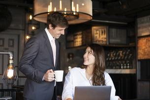 ビジネストークをするアメリカ人男性と日本人女性の写真素材 [FYI04317037]