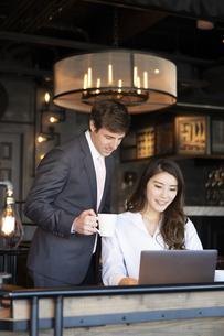 ビジネストークをするアメリカ人男性と日本人女性の写真素材 [FYI04317038]