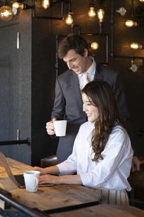 ビジネストークをするアメリカ人男性と日本人女性の写真素材 [FYI04317039]