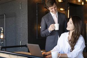 ビジネストークをするアメリカ人男性と日本人女性の写真素材 [FYI04317041]
