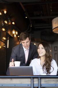 ビジネストークをするアメリカ人男性と日本人女性の写真素材 [FYI04317045]