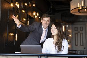 ビジネストークをするアメリカ人男性と日本人女性の写真素材 [FYI04317046]