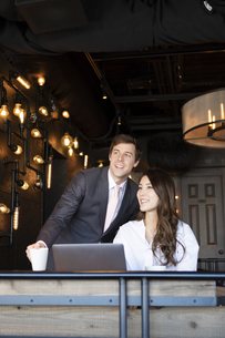 ビジネストークをするアメリカ人男性と日本人女性の写真素材 [FYI04317047]