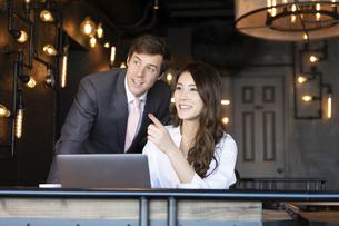 ビジネストークをするアメリカ人男性と日本人女性の写真素材 [FYI04317048]