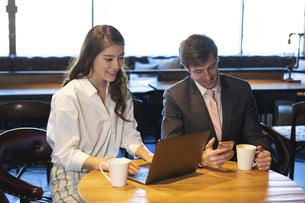 ビジネストークをするアメリカ人男性と日本人女性の写真素材 [FYI04317049]