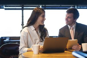 ビジネストークをするアメリカ人男性と日本人女性の写真素材 [FYI04317050]