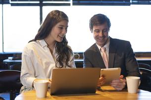 ビジネストークをするアメリカ人男性と日本人女性の写真素材 [FYI04317051]