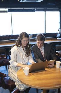 ビジネストークをするアメリカ人男性と日本人女性の写真素材 [FYI04317052]