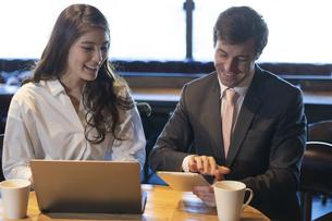 ビジネストークをするアメリカ人男性と日本人女性の写真素材 [FYI04317053]