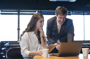 ビジネストークをするアメリカ人男性と日本人女性の写真素材 [FYI04317054]