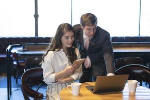 ビジネストークをするアメリカ人男性と日本人女性の写真素材 [FYI04317058]