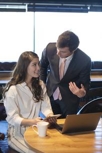 ビジネストークをするアメリカ人男性と日本人女性の写真素材 [FYI04317059]