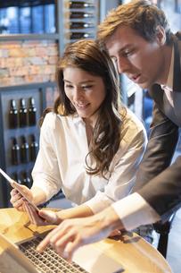 ビジネストークをするアメリカ人男性と日本人女性の写真素材 [FYI04317060]