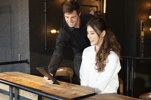 アメリカ人バーテンダーと客の日本人女性の写真素材 [FYI04317117]