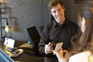 レジ対応をする男性と支払いをする女性の写真素材 [FYI04317127]