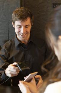 レジ対応をする男性と支払いをする女性の写真素材 [FYI04317128]