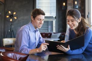 カフェでメニューを見るカップルの写真素材 [FYI04317130]