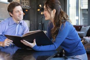 カフェでメニューを見るカップルの写真素材 [FYI04317133]