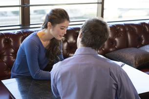 カフェでメニューを見るカップルの写真素材 [FYI04317134]