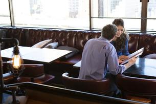 カフェでメニューを見るカップルの写真素材 [FYI04317135]