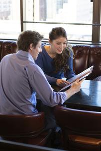 カフェでメニューを見るカップルの写真素材 [FYI04317136]