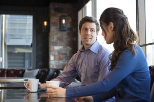 カフェで談笑するカップルの写真素材 [FYI04317146]