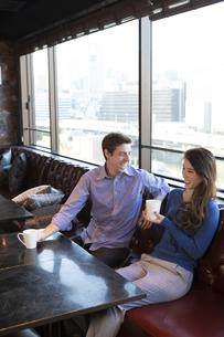 カフェで談笑するカップルの写真素材 [FYI04317152]