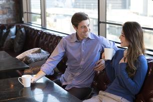 カフェで談笑するカップルの写真素材 [FYI04317153]