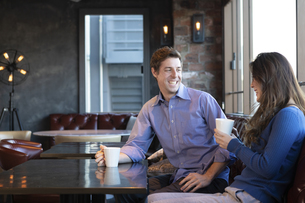 カフェで談笑するカップルの写真素材 [FYI04317155]