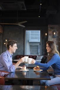 カフェで談笑するカップルの写真素材 [FYI04317159]