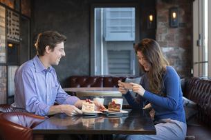 カフェで談笑するカップルの写真素材 [FYI04317162]