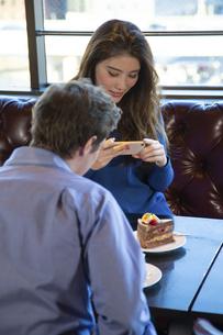 カフェで談笑するカップルの写真素材 [FYI04317165]