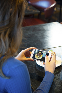 ケーキの写真を撮る女性の写真素材 [FYI04317168]