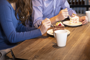 カフェでケーキを食べるカップルの写真素材 [FYI04317194]