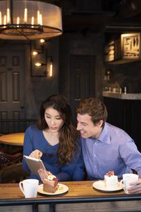 タブレットを見るカップルの写真素材 [FYI04317205]