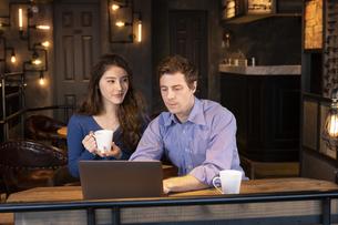 PCを見るカップルの写真素材 [FYI04317215]