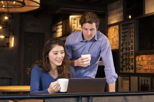 PCを見るカップルの写真素材 [FYI04317219]