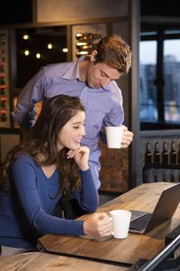 PCを見るカップルの写真素材 [FYI04317222]