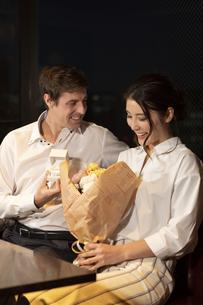 花束を持つ女性と指輪を差し出す男性の写真素材 [FYI04317249]