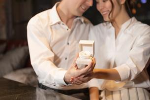 婚約指輪を持って見つめ合うカップルの写真素材 [FYI04317251]